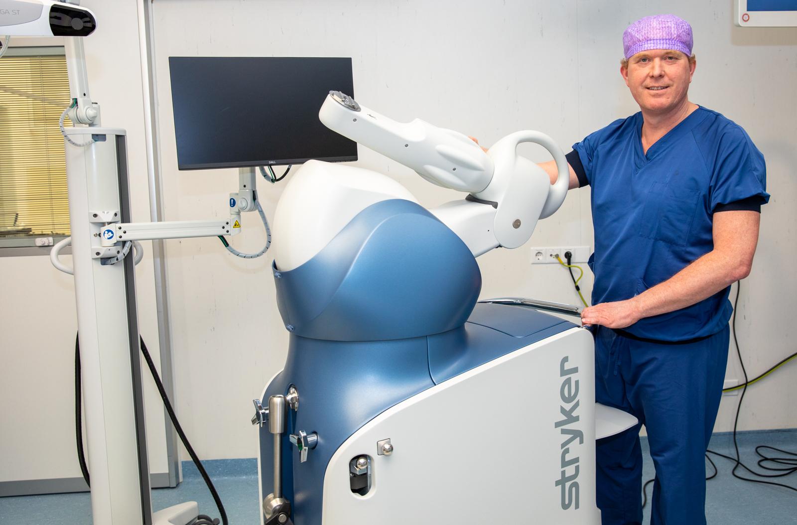 Orthopedisch chirurg Martijn van Dijk met de robotarm