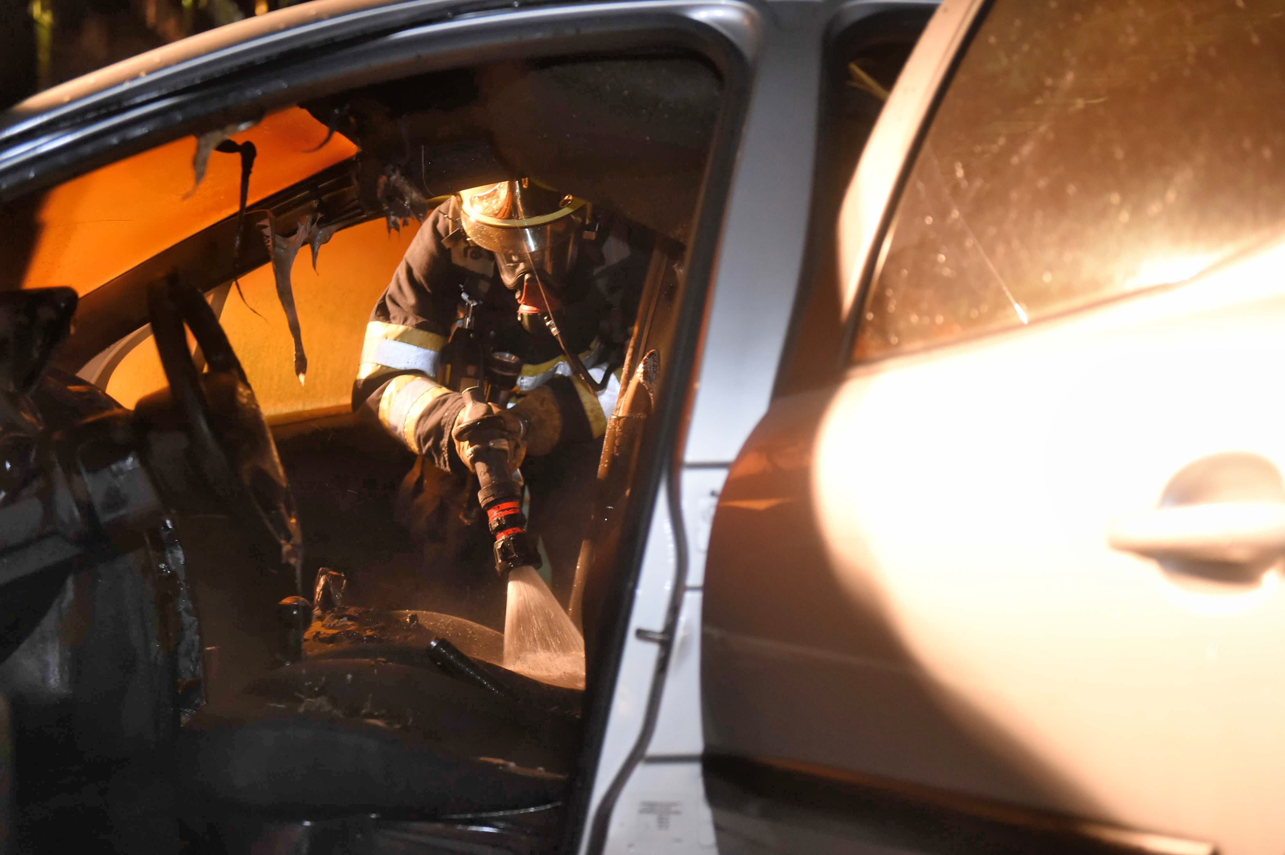 Foto van branweerman bij autobrand