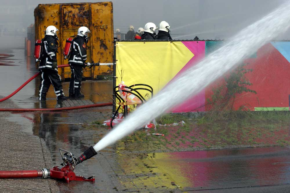 Foto van brandweerman blussen slang   Archief EHF