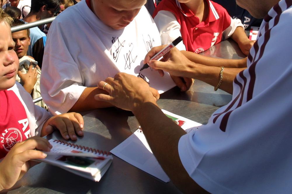 Foto van ajacied die handtekening zet op shirt | Archief EHF
