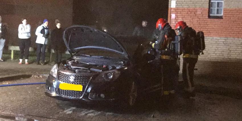 Brandweerlieden bij uitgebrande auto