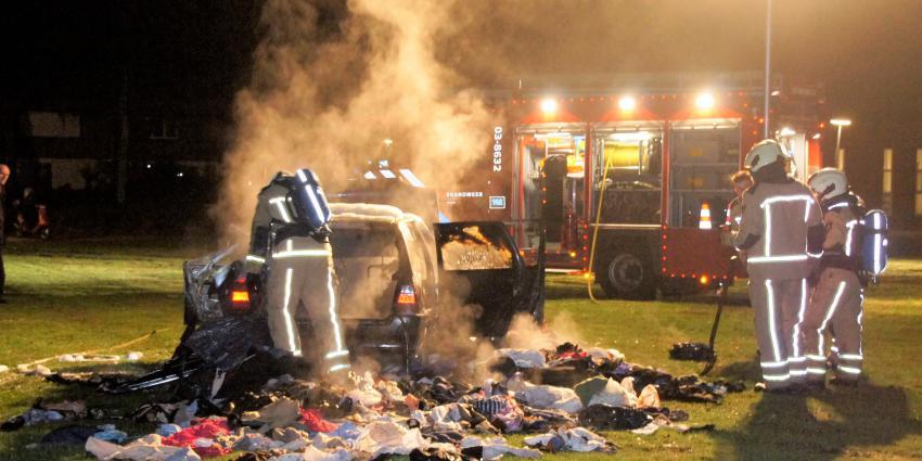 Auto vol met kleding in brand