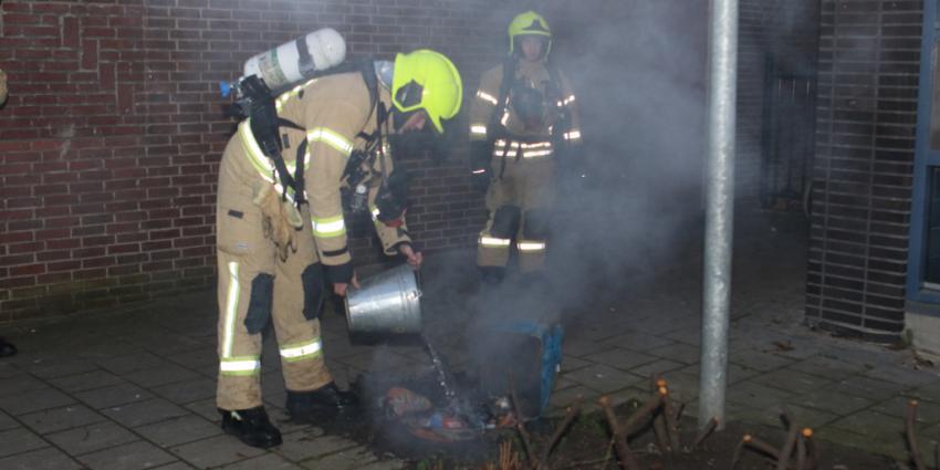 Brandweer blust brand met emmer