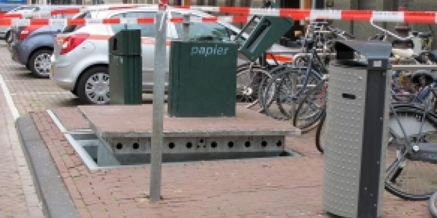 Man klem in ondergrondse papiercontainer na weggooien staatslot