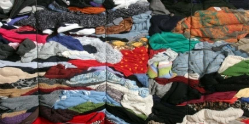 Man past zijn 'nieuwe outfit' in container voor gebruikte kleding