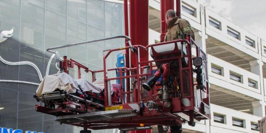 Ambulancemedewerkers met patient vast in lift