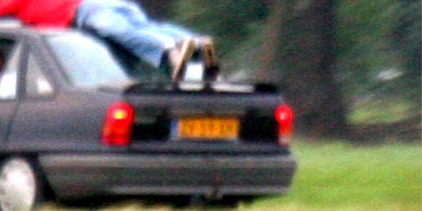 Foto van man op autodak
