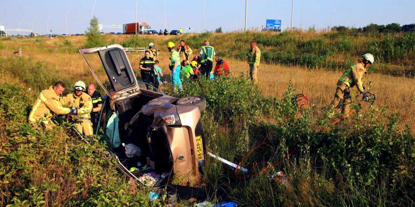 Vrouw met auto van talud snelweg A58 bij Eindhoven