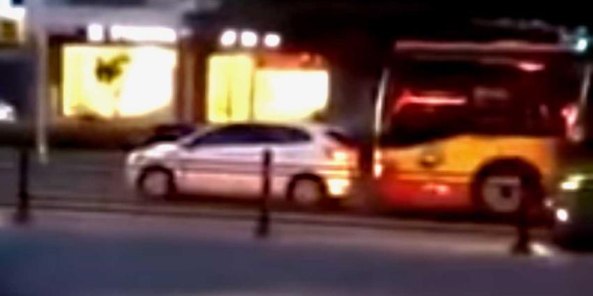 Personenauto rammende bus rijdt over benen automobilist