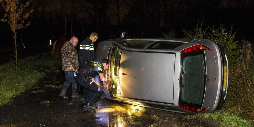 Auto op zijn kant in Oirschot, buurtbewoner schiet te hulp