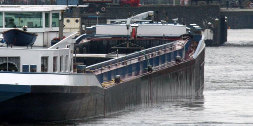 Binnenvaartschipper met slok op vaart tegen visserskotter