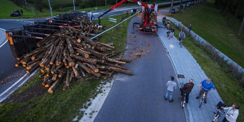 Vrachtwagen geladen met boomstammen kantelt op rotonde in Best