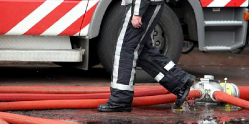 Brandweerwagen onderweg naar brand gekanteld en tegen woning gebotst