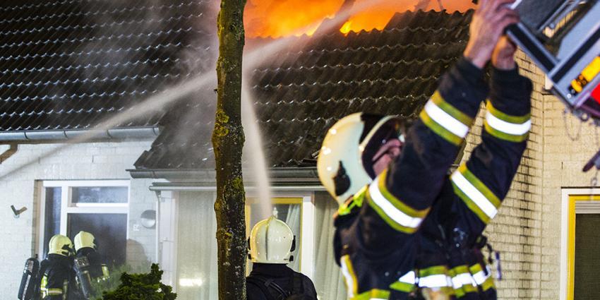 Vlammen slaan uit dak woning