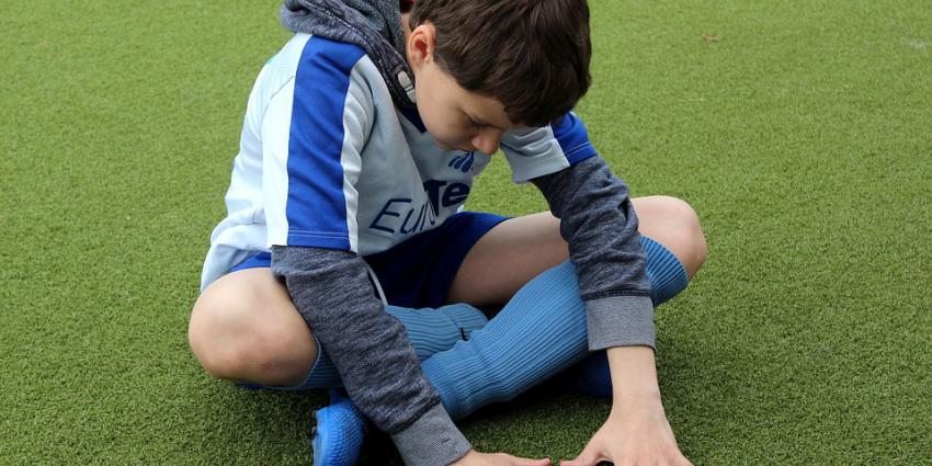 Jongen alleen op voetbalveld