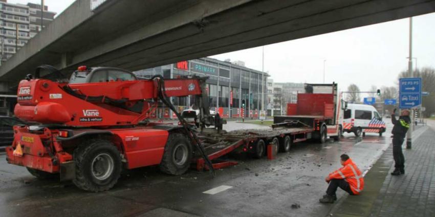 Graafmachine van vrachtwagen afgevallen