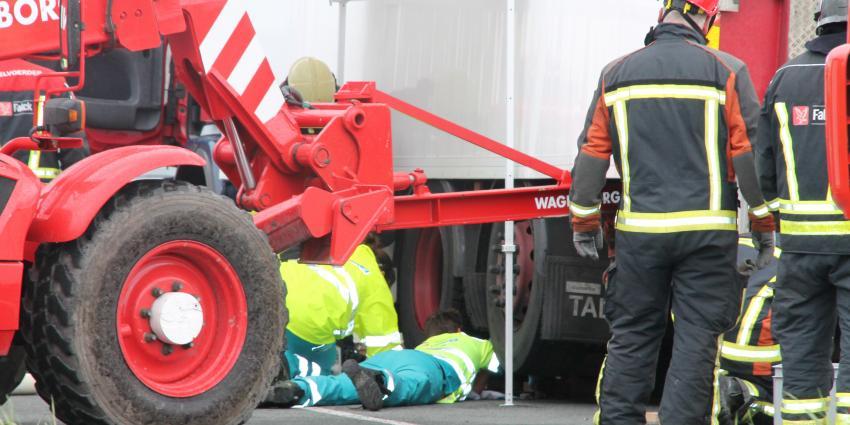 Persoon bekneld onder vrachtwagen