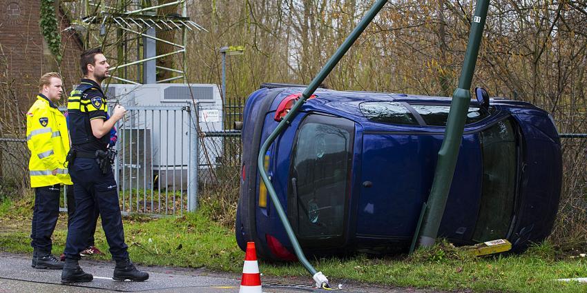 Auto op zijn kant tegen lantaarnpaal