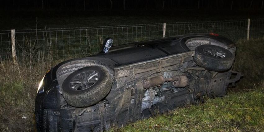 Jeep ramt lantaarnpaal en belandt op zijn kant in sloot
