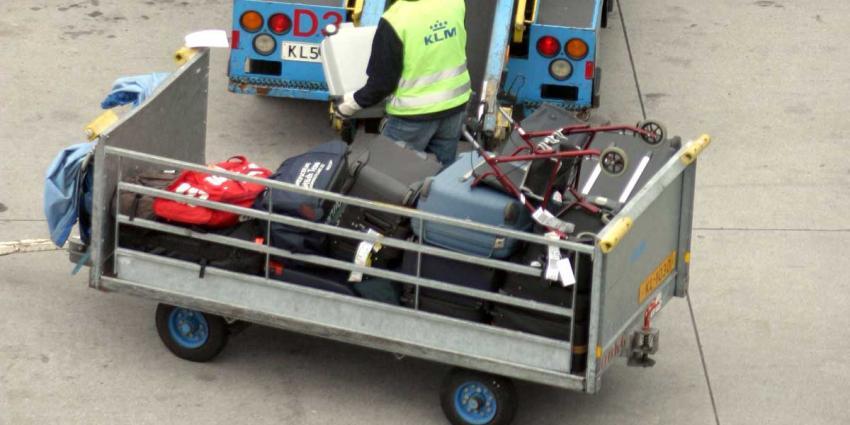Medewerker KLM bij bagageband