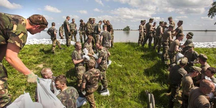 Foto van militairen die dijk verstevigen   Min. Defensie