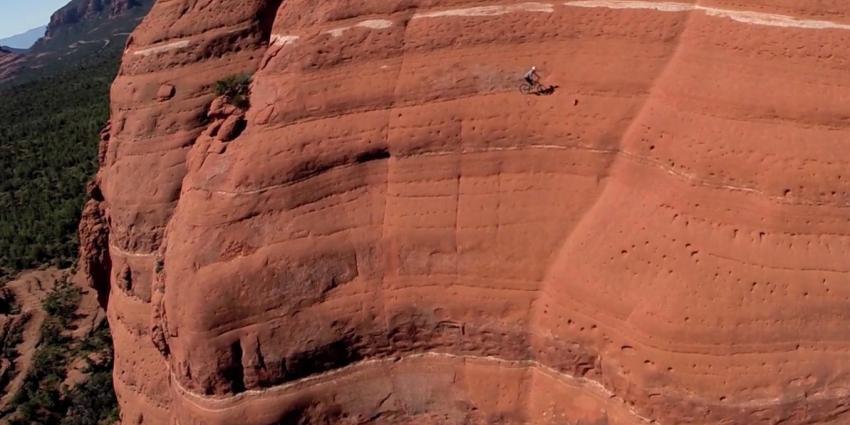 Mountainbiker fietst op levensgevaarlijke richel van steile berg