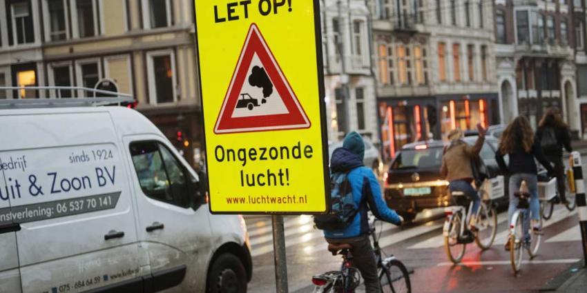 Actievoerders plaatsen verkeersborden tegen ongezonde lucht in steden