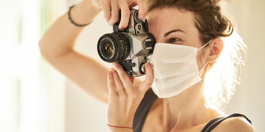 Vrouw met mondkapje en fototoestel