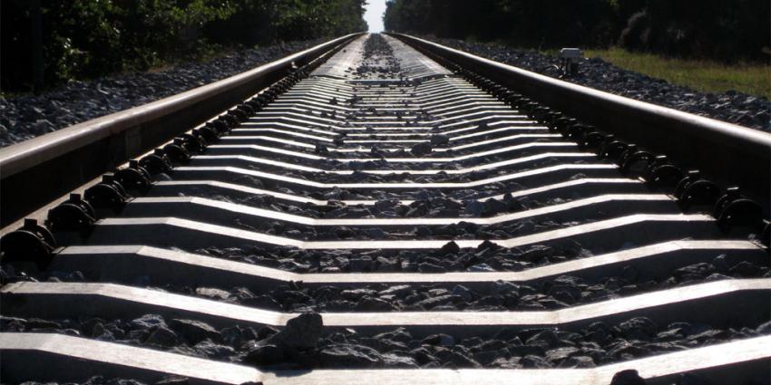Jongens leggen stenen op rails