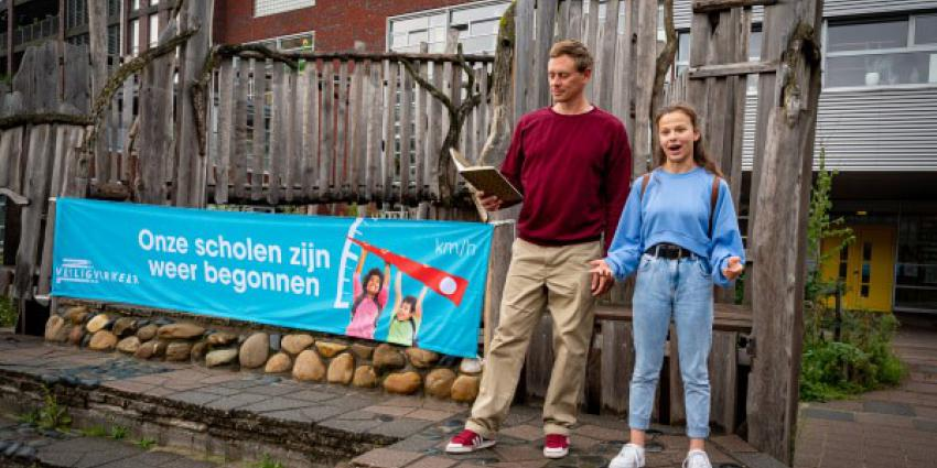 """Justin Samgar en scholier Anna dragen het gedicht """"Onze scholen zijn weer begonnen"""" voor bij basisschool de Hasselbraam in Amsterdam."""