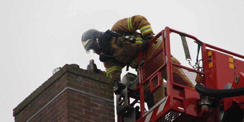 Brandweerman bezig met schoorsteenbrand