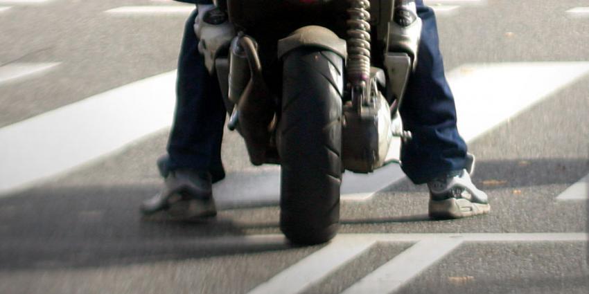 Blowende bromfietser rijdt door rood terwijl politie toekijkt