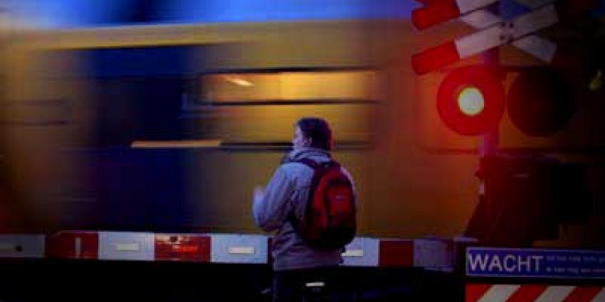 Foto van fietser voor slagboom spoorovergang trein | Archief EHF