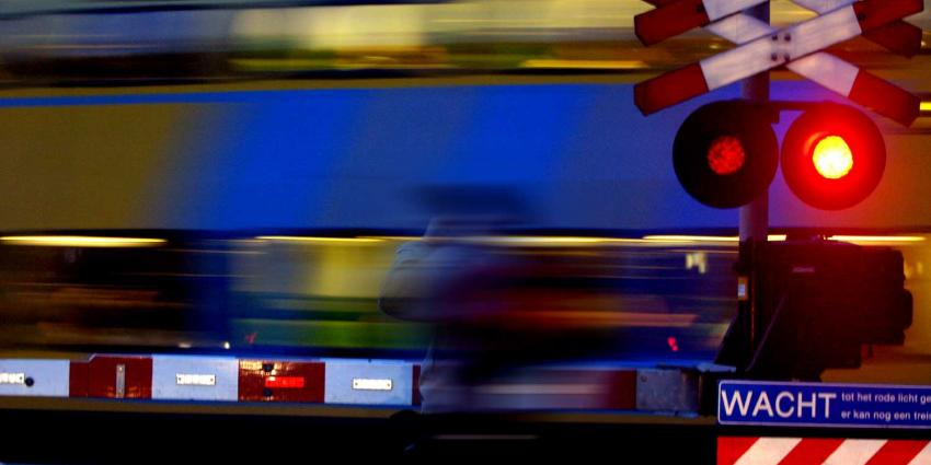 Foto van spoorwegovergang slagboom donker trein | Archief EHF