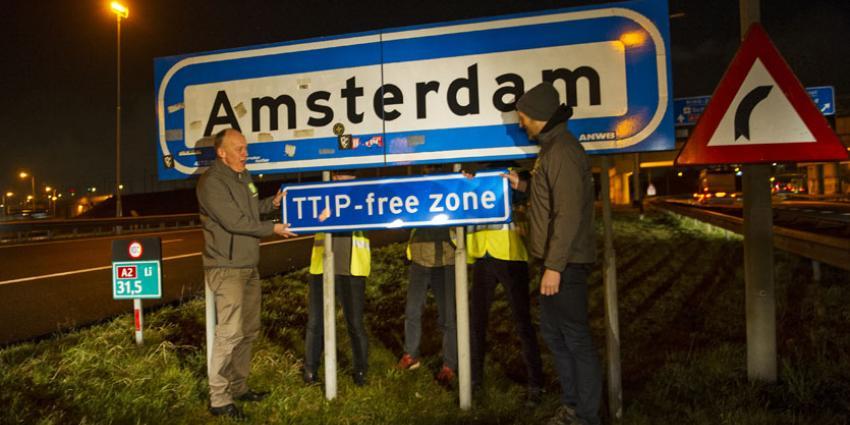 Actievoerders plaatsen verkeersbord 'TTIP free zone'