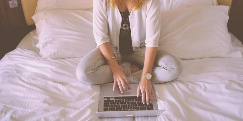 Vrouw op bed achter laptop