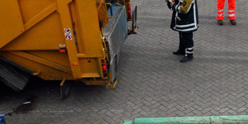Vuilnisman raakt onder wiel vuilniswagen
