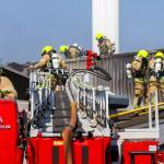 Foto van brandweerlieden op ladderwagen