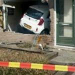 Vrouw rijdt met auto door gevel woonkamer binnen
