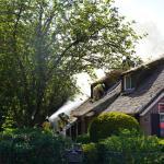 Brandweermannen halen rieten dak uit