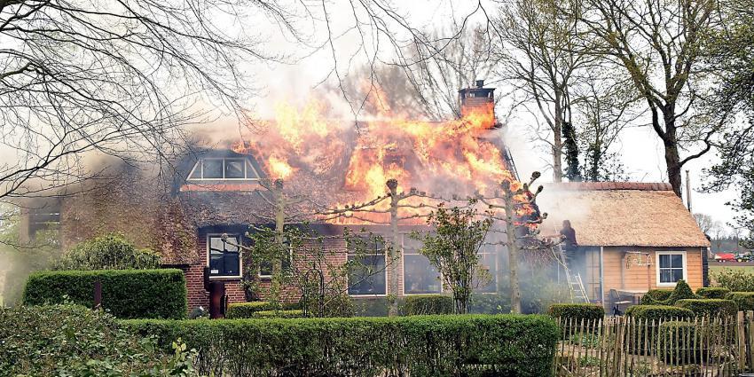 Woning met rietenkap in brand