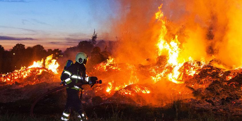 Brandweer druk met blussen stapel afval van boomkwekerij