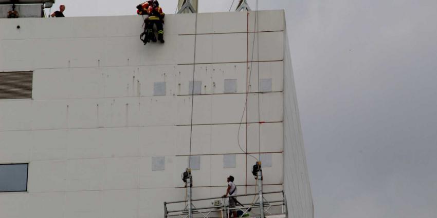Glazenwasser op eenzame hoogte vast in bakje op 12e etage