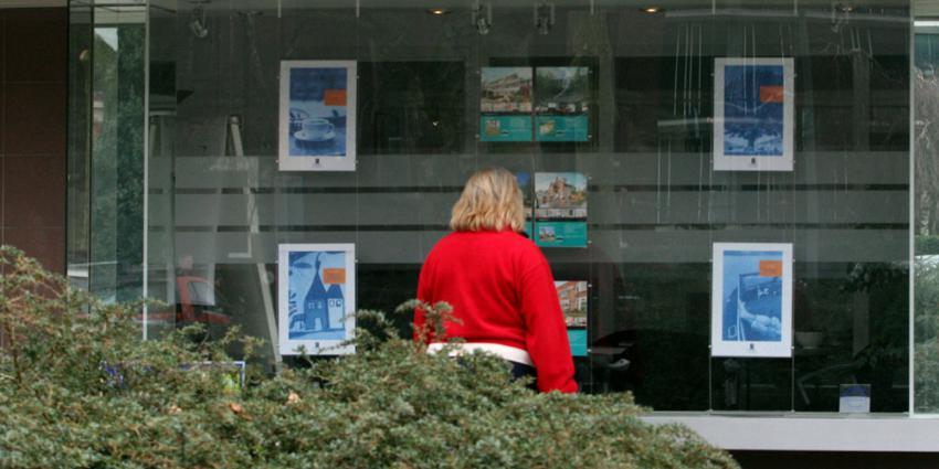 Vrouw bekijkt woningen in etalage