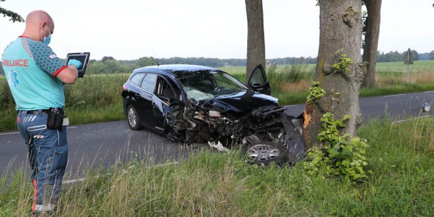 Ambulancemedewerker neemt foto van gecrashte auto