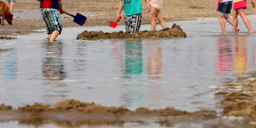 Foto van met water spelende kinderen op strand   Archief EHF