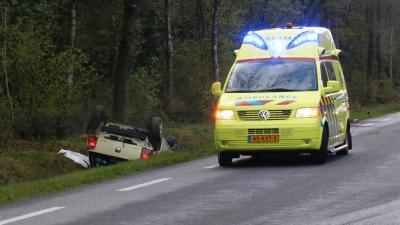 Vrouw met auto over de kop in sloot en bekneld