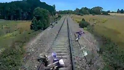 Motorcrosser springt voor zijn leven van treinrails