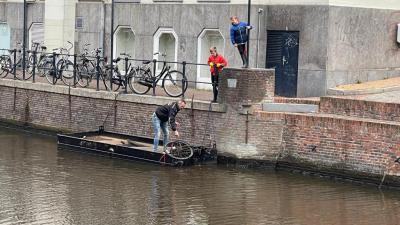 een oude fiets wordt uit het water gehaald