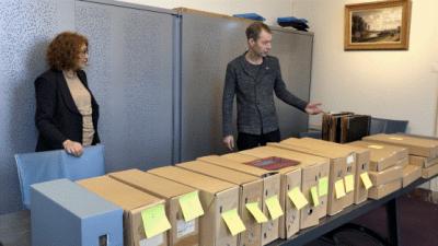 Spoorwegmuseumconservator Evelien Pieterse (l) overhandigt het archief aan Victor Lansink van Het Utrechts Archief